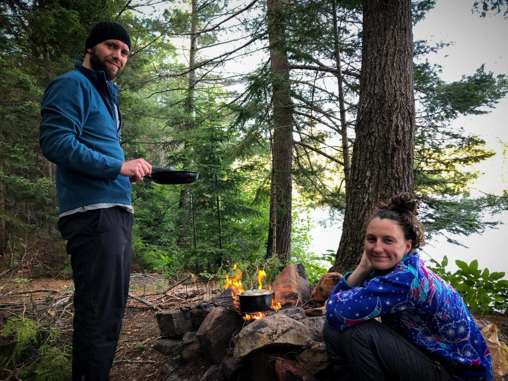 Two hikers cooking over a fire
