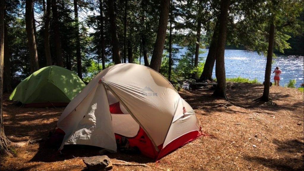Two tent set up at the campsite, with Provoking Lake shimmering in the background