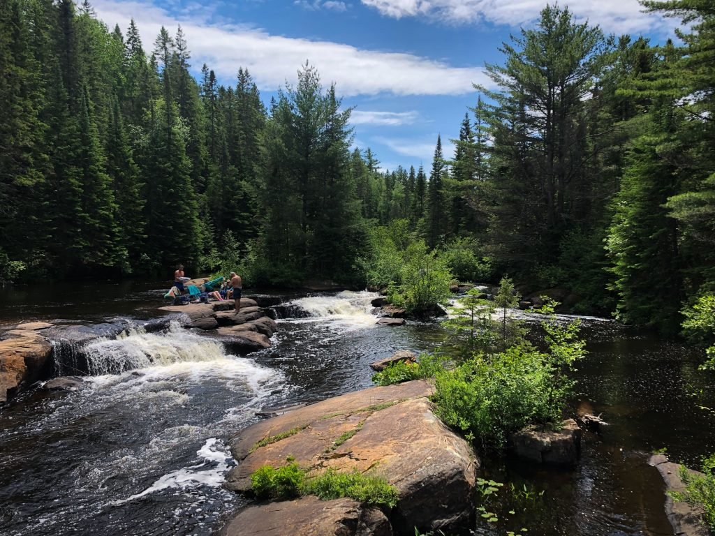 People sitting in camping chairs at Provoking Falls, a stop on the Highland Backpacking Trail