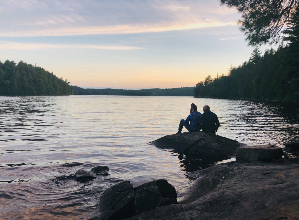 Sunset over Head Lake, two people sitting on a rock in the foreground